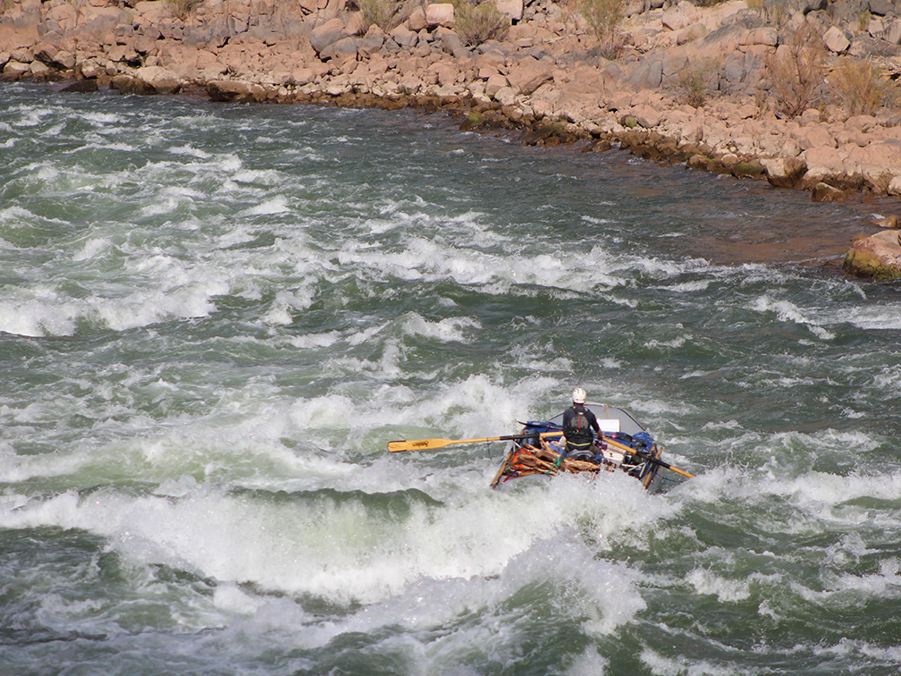 A raft running through the center of Deubendorff Rapid in the Grand Canyon
